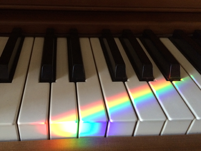 Rainbow piano keys illuminated by a prism beam from the rainbow sundial on the window sill