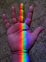 Rainbow colors from a Spectra sundial on the window sill kiss the maker's hand. Feel the color...Touch the rainbow!