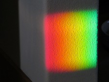 Rainbow colors on the wall coming from a rainbow sundial on the window sill
