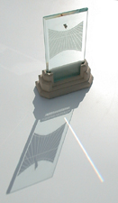 Spectra sundial with its overall shadow and rainbow prism beam